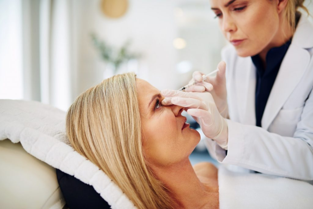 Doctor injecting botox into a mature woman's forehead